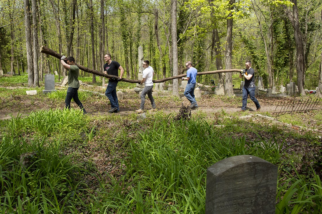 Volunteers carrying a large limb.