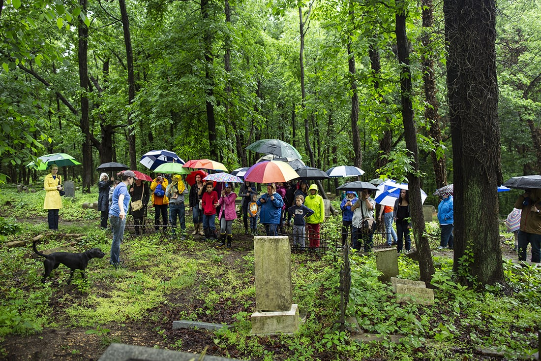 A group of people in colorful raingear surrounded by green leaves gathers to hear Erin Hollaway Palmer talk about the cemetery.