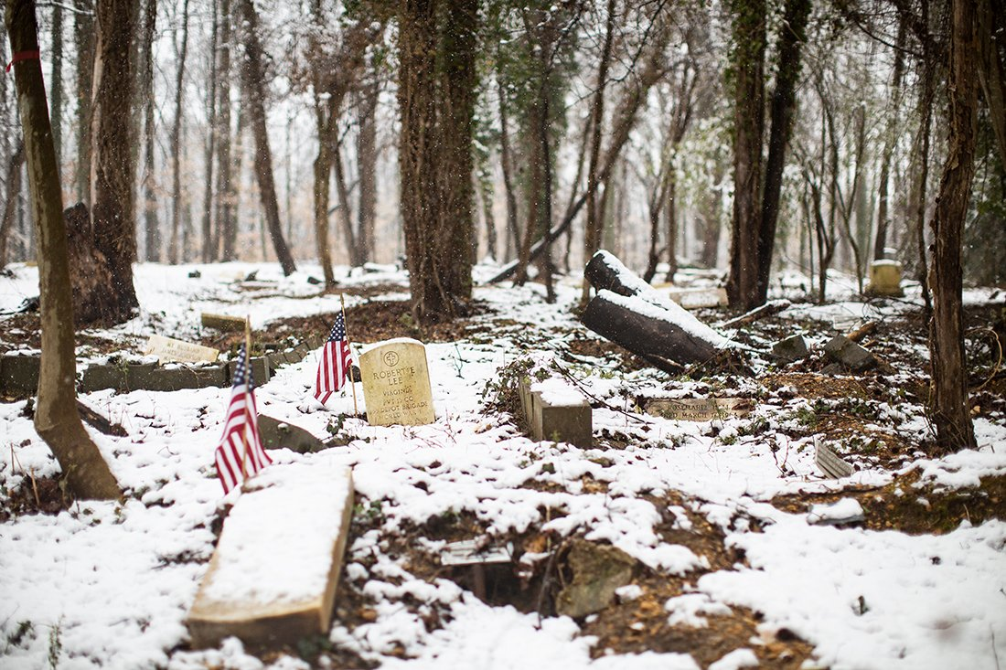A snowy day wiht flags near veterans' markers.