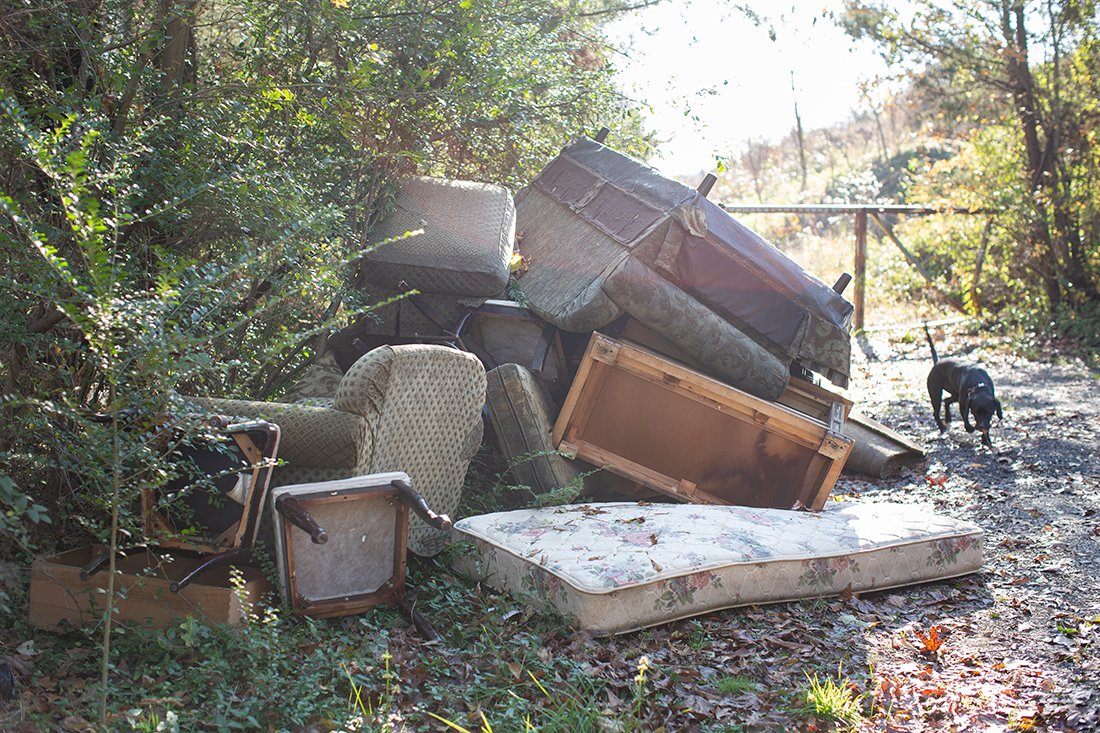A large pile of illegally dumped furniture and mattresses.